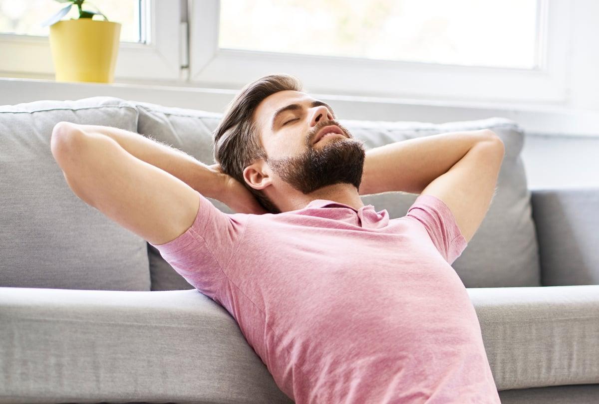 Mann mit geschlossenen Augen auf dem Sofa