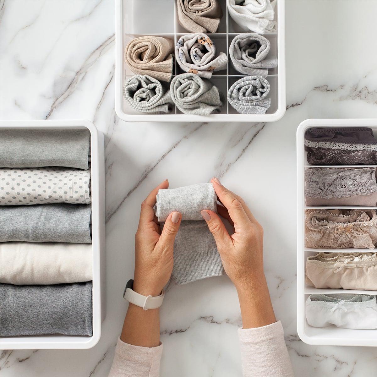 Frau legt Kleidungsstücke in Ablagebox
