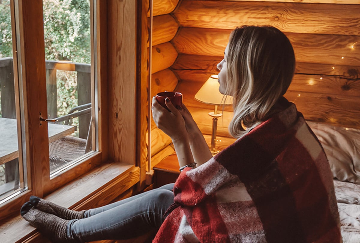 Frau mit Teetasse am Fenster
